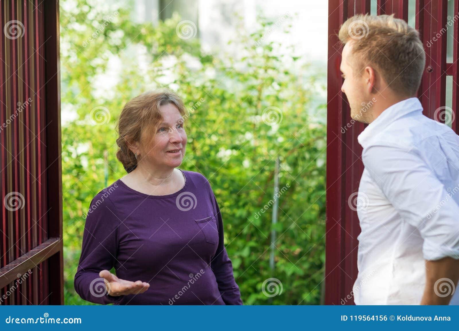 Sąsiad dyskutują wiadomość, stoi przy ogrodzeniem Starsza kobieta opowiada z młodym człowiekiem
