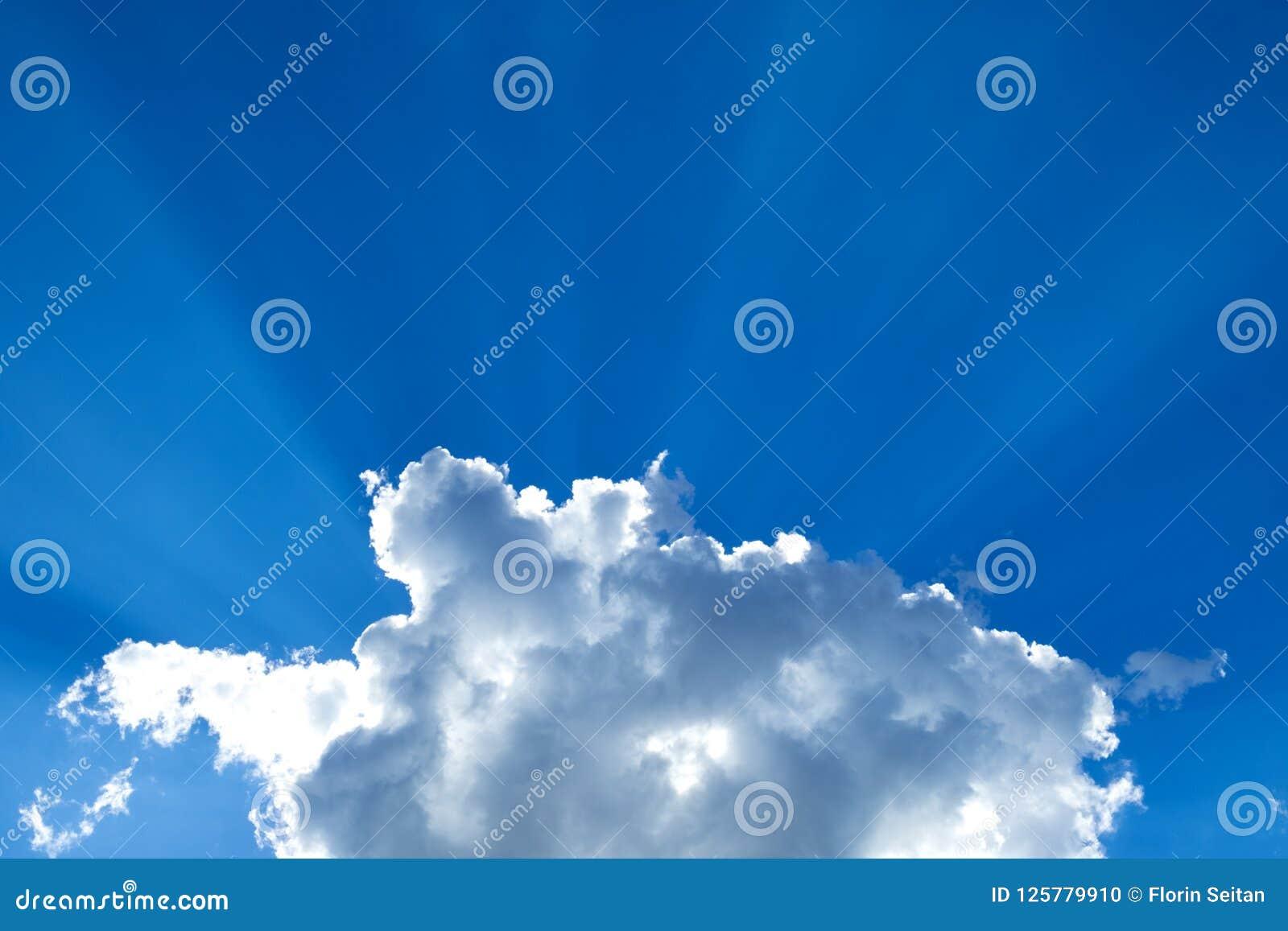 Słońce promienieje łamanie przez cumulus chmury