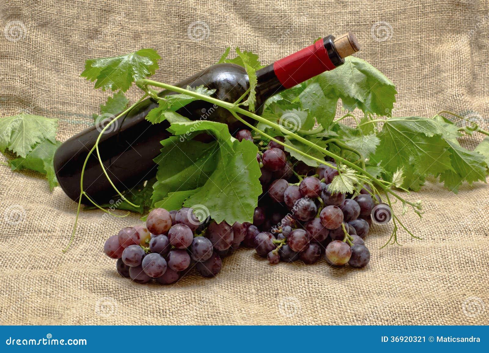 Słodcy czerwoni winogrona z butelką czerwone wino.