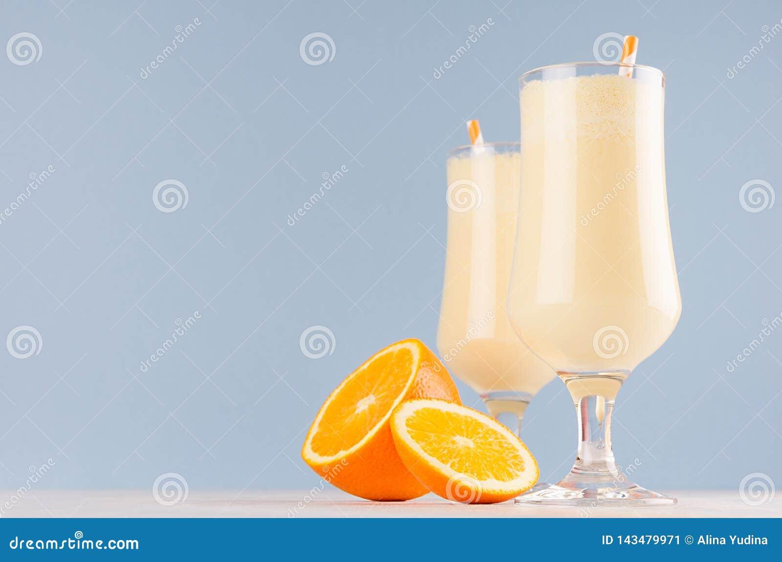 Słodcy rozochoceni pomarańcz milkshakes w dwa plasterków szkło dekorującej owoc, pasiaste słoma na lekkim pastelowym błękitnym tl