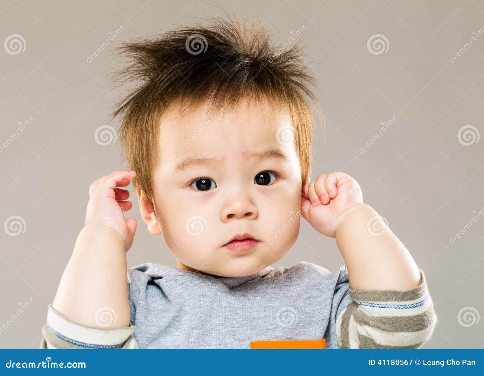Słodka chłopiec z ręka dotyka ucho