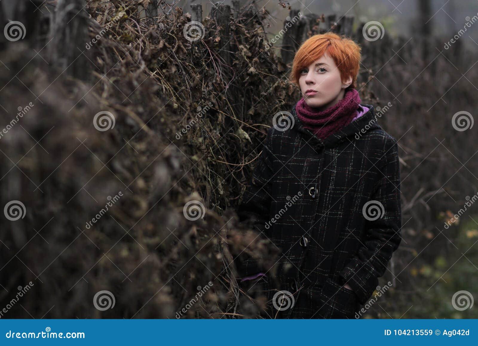 Słodka miedzianowłosa dziewczyna w czarnym żakiecie purpura dziającym szaliku i stoi ogrodzeniem przerastającym z winoroślą lub b