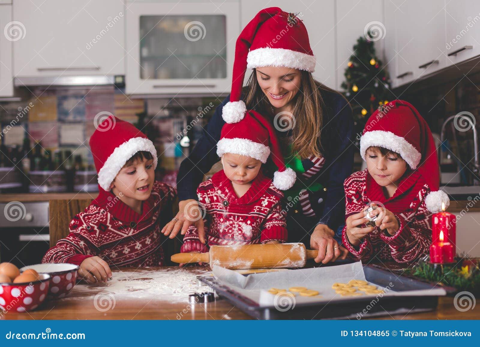 Słodki berbecia dziecko i jego stary brat, chłopiec, pomaga mamusi narządzania Bożenarodzeniowi ciastka w domu