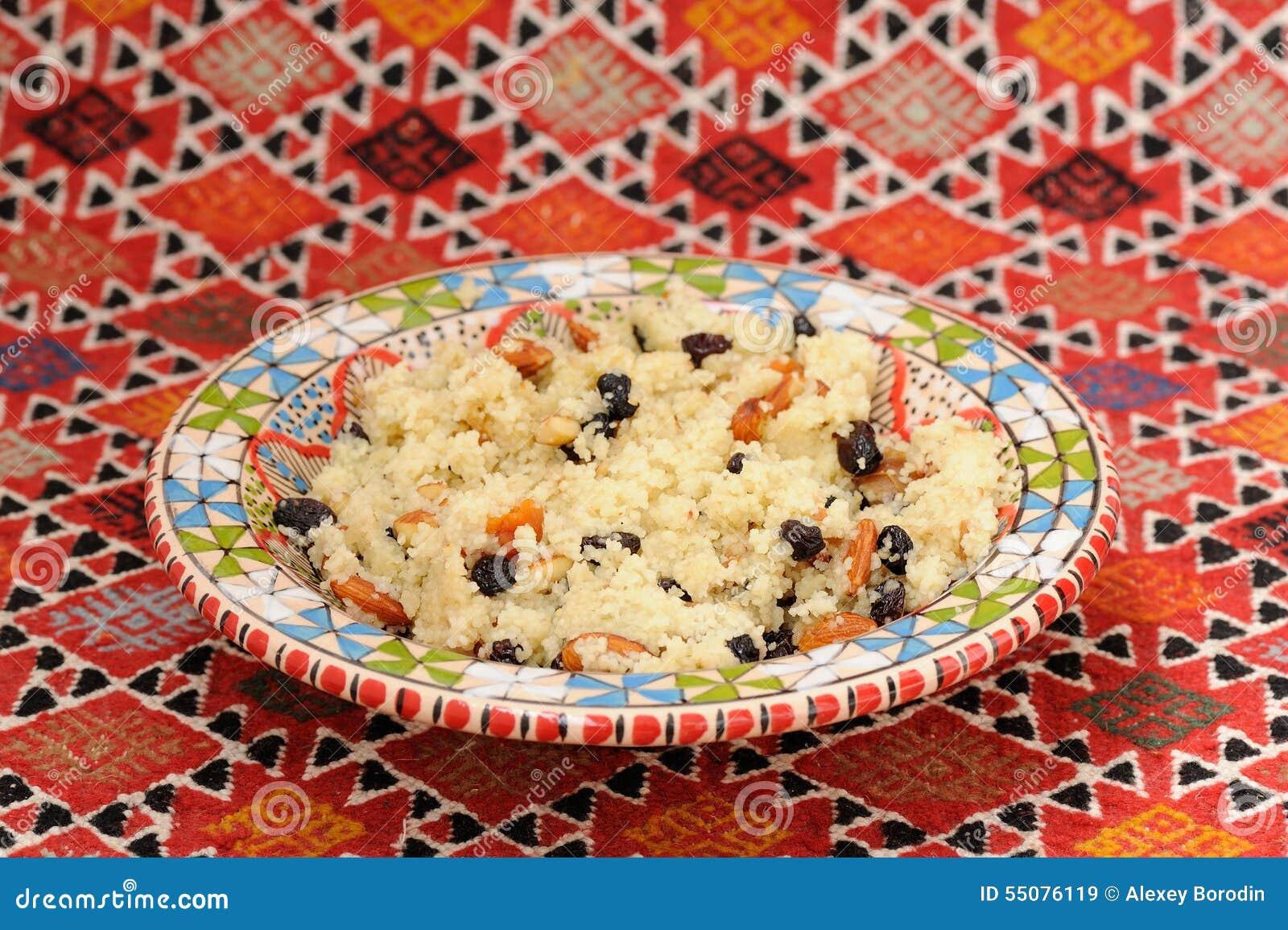 Słodki couscous z migdałem i wysuszonymi owoc na czerwonym handmade karpiu