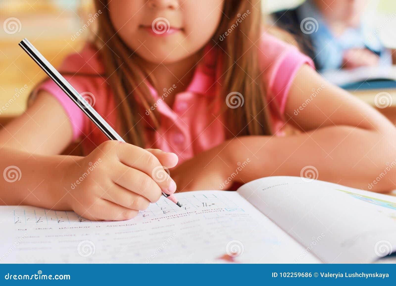 Słodki Kaukaski dziecko w szkole przy biurkiem pisze w notatniku