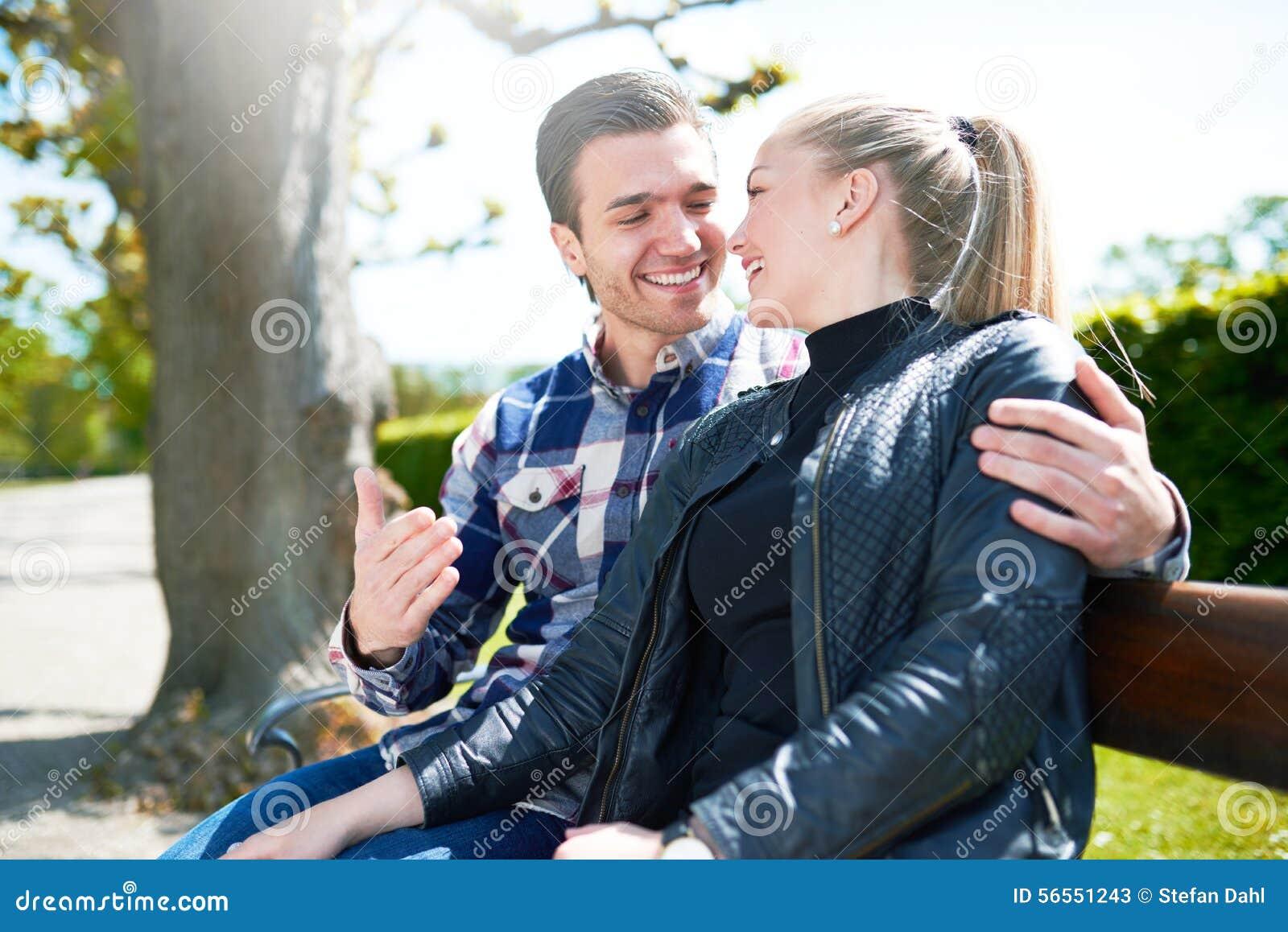 Słodki potomstwo pary obsiadanie na ławce przy parkiem