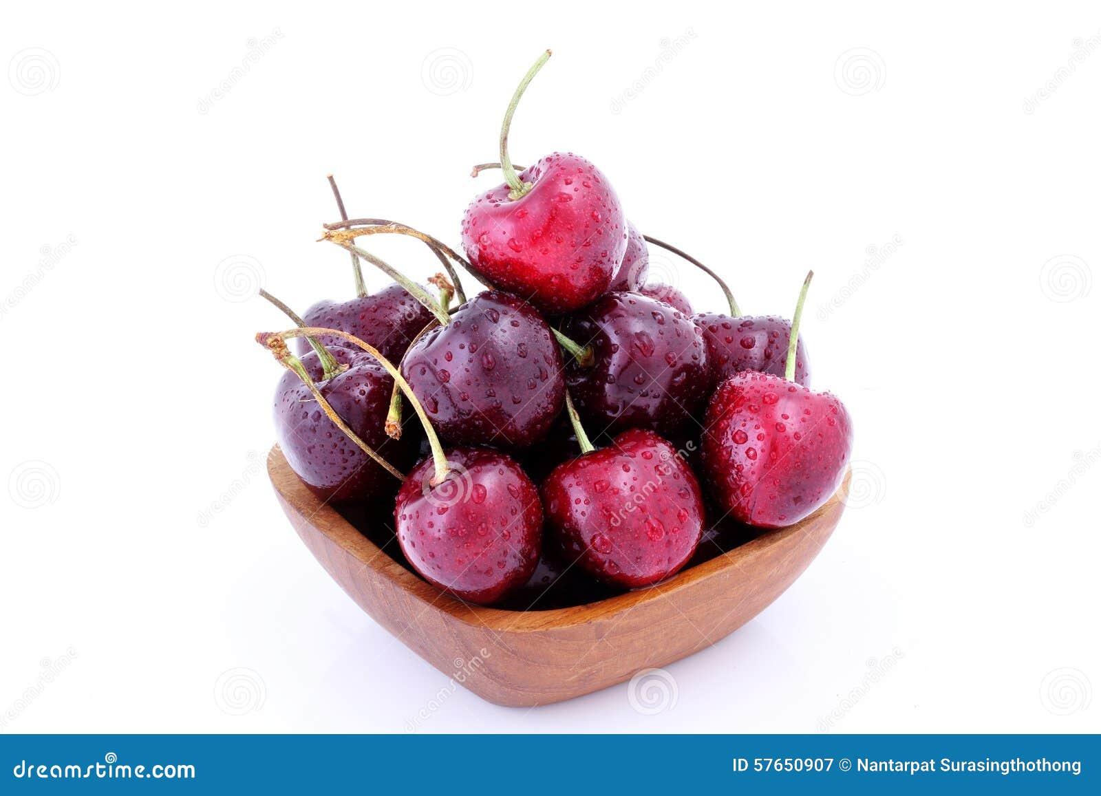 Słodkie wiśnie w drewnianym pucharze odizolowywającym na białym tle