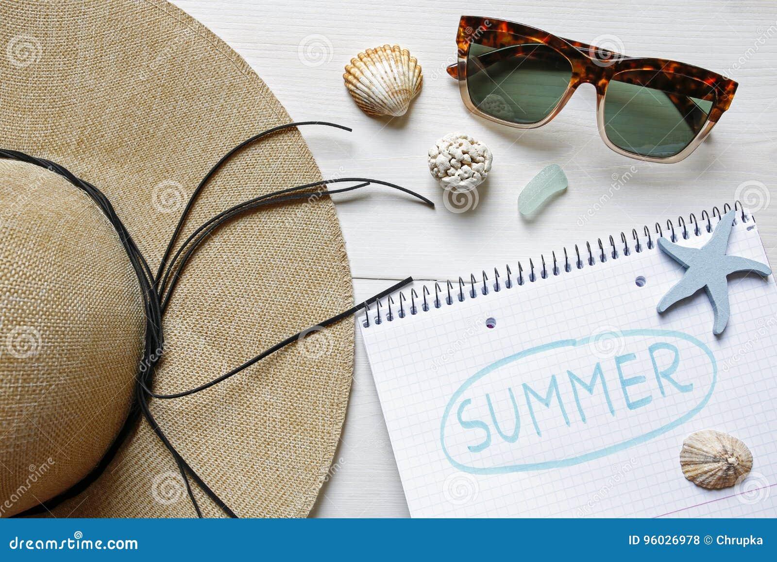 Słomiany kapelusz, seashells, okulary przeciwsłoneczni i notatnik na bielu stole,