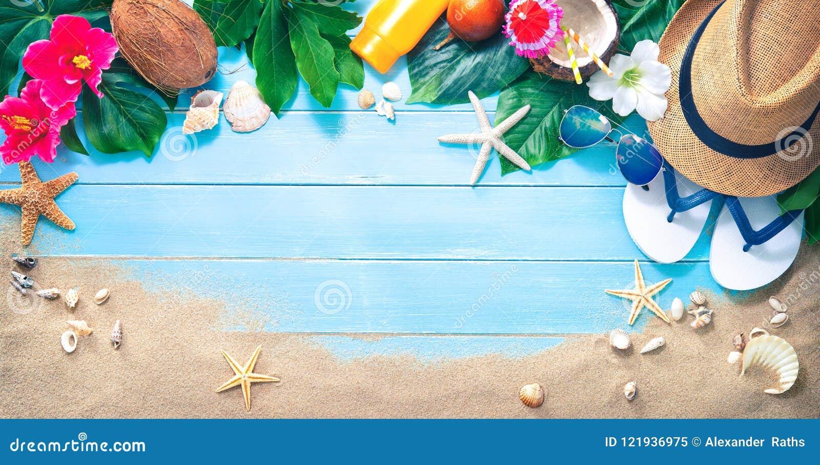 Słomiany kapelusz z egzotycznym koktajlem i okulary przeciwsłoneczni na piasku wyrzucać na brzeg