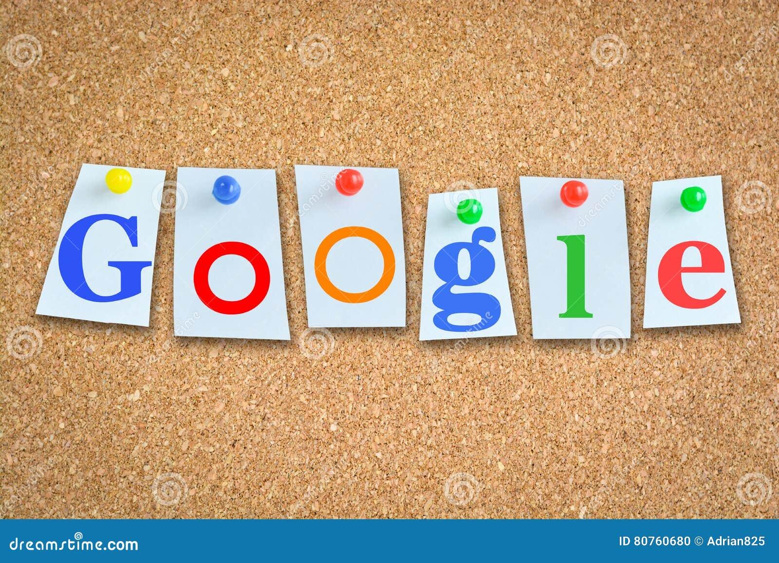 Słowo Google na korkowym billboardzie z notatką tapetuje i szpilki