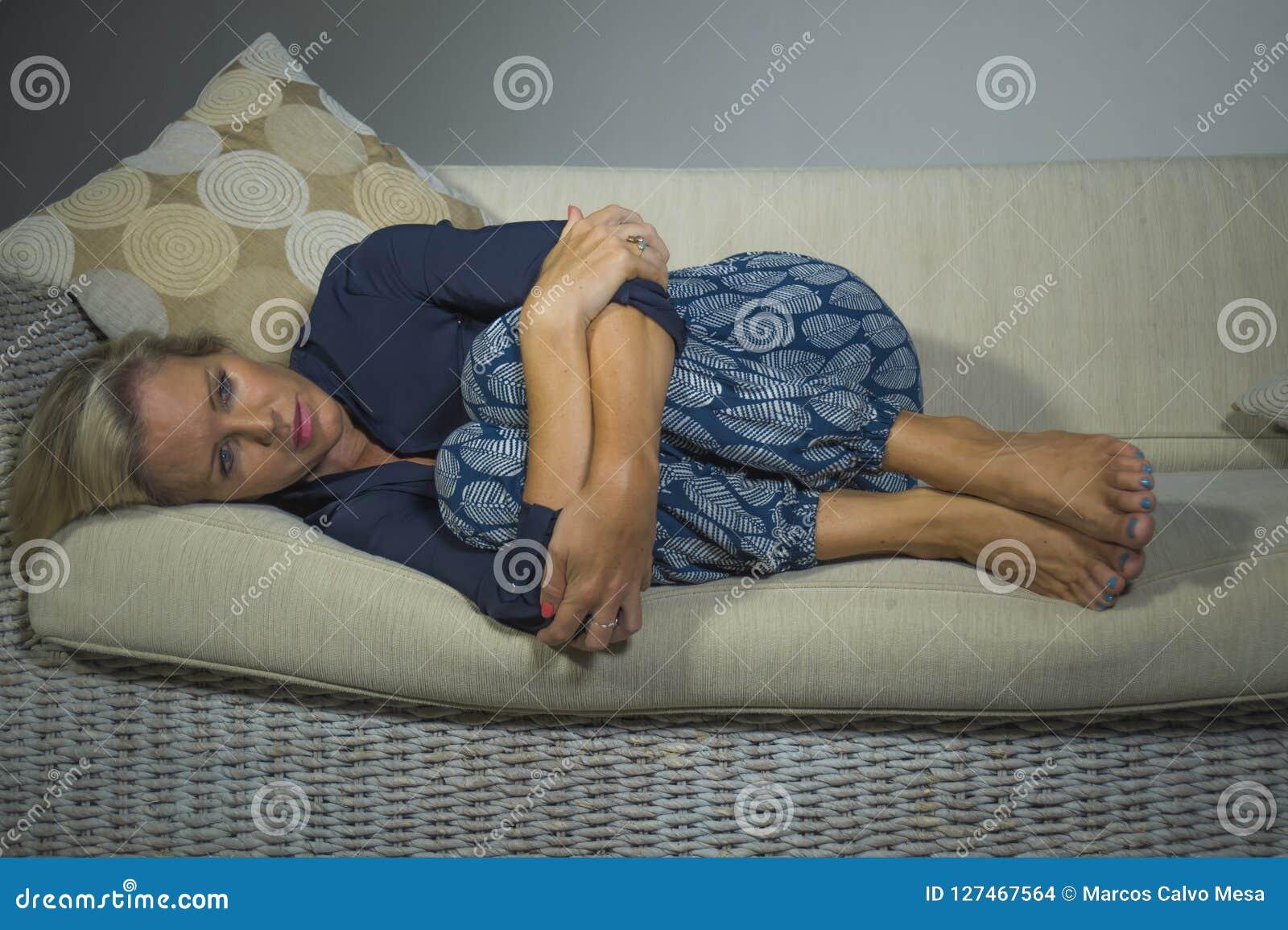 40s沮丧的和急切美丽的白肤金发的妇女感觉被挫败的在家说谎的遭受的消沉和忧虑问题沙发co