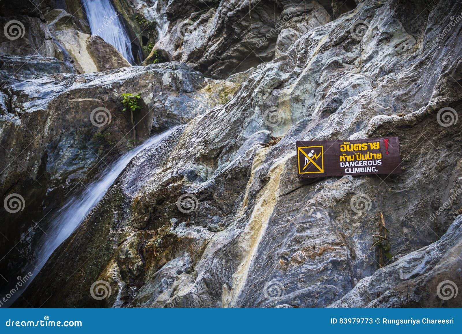 S élever dangereux de panneau d avertissement à la cascade avec des pierres