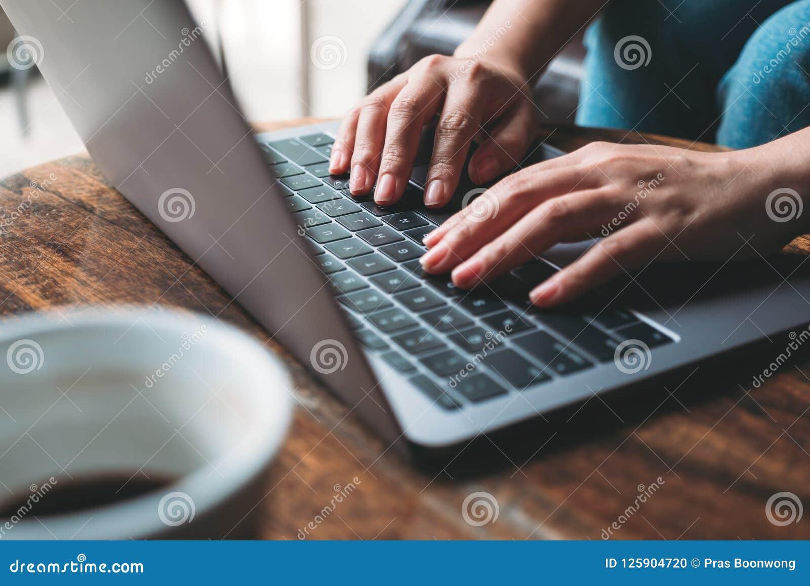 ` S женщины вручает работу и печатать на клавиатуре компьтер-книжки с кофейной чашкой на деревянном столе