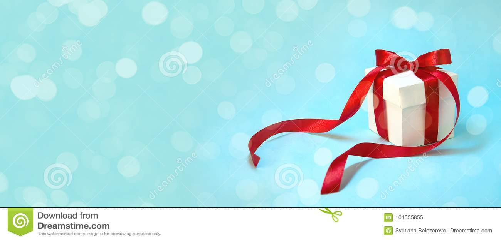 ` S подарка рождества в белой коробке с красной лентой на свете - голубой предпосылке Знамя состава праздника Нового Года скопиру