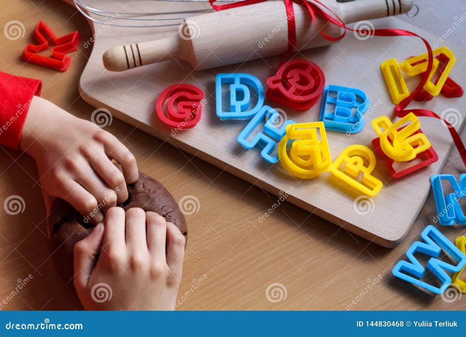 Руки маленькой девочки замешивая тесто Варить традиционные печенья пасхи Концепция еды пасхи
