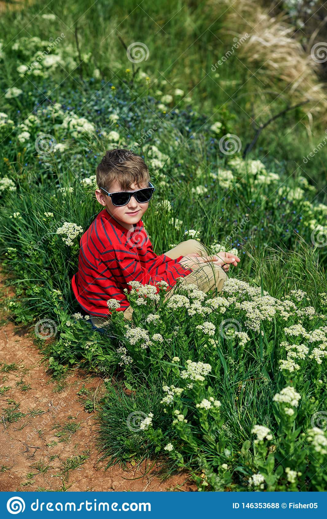 S?ance de repos de gar?on sur l herbe pendant une promenade de pays
