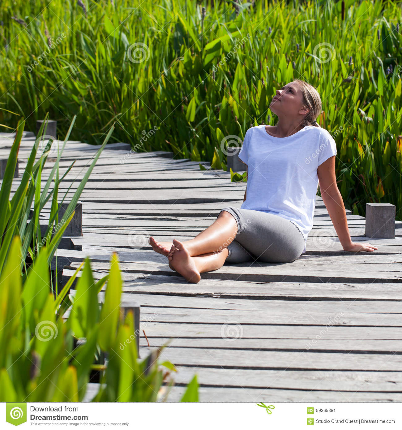 20s Blond Girl Lying In The Sun Relaxing Outdoors Stock