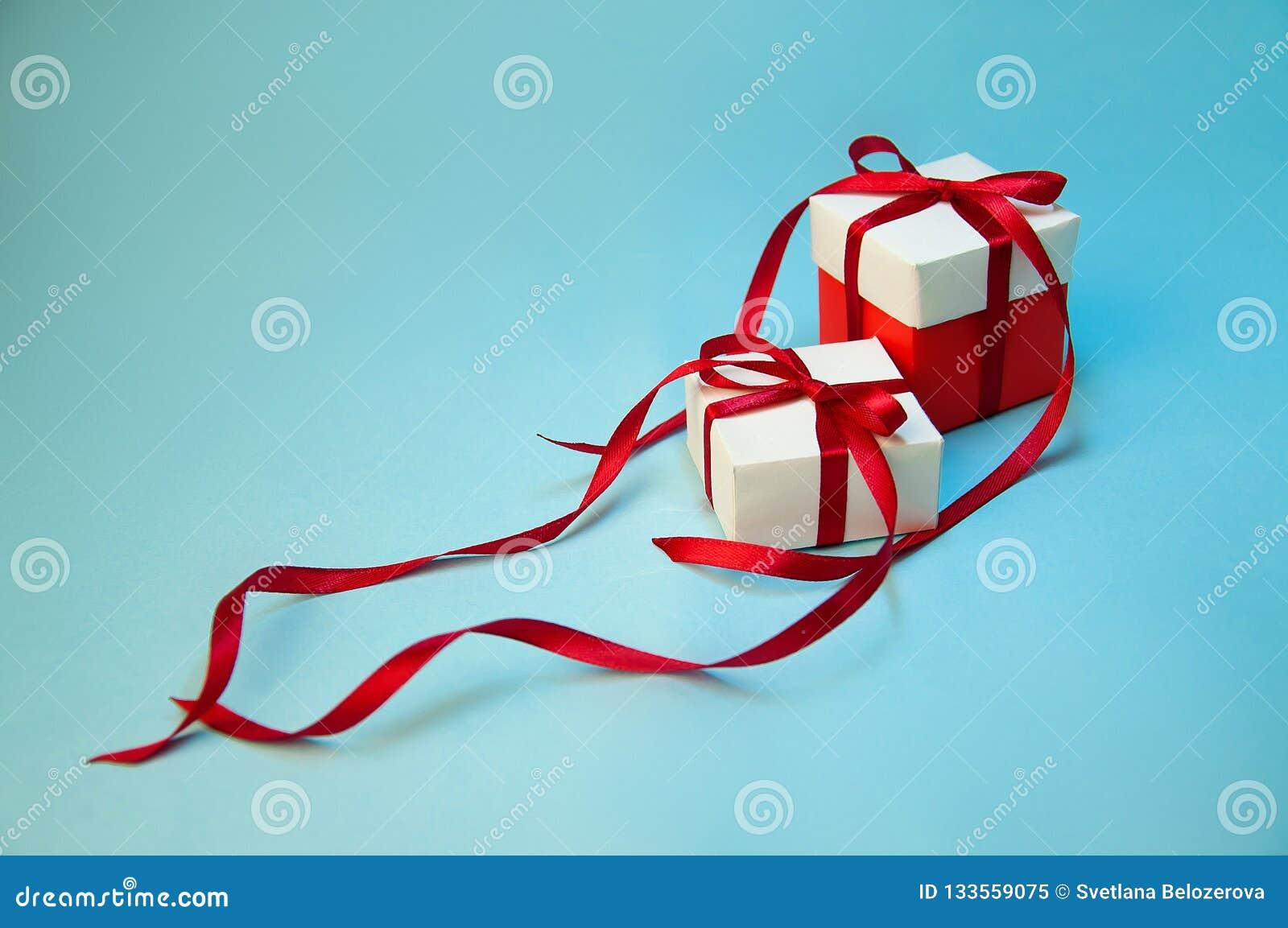 ` S de cadeau de Noël dans le boîtier blanc avec le ruban rouge sur le fond bleu-clair Composition en vacances de nouvelle année