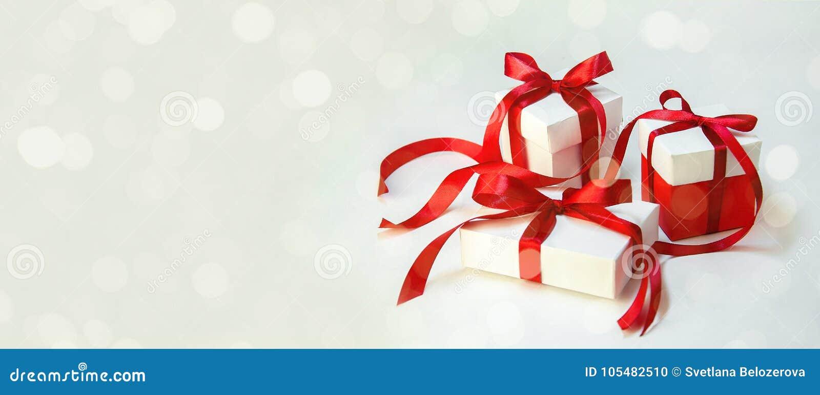 ` S de cadeau de Noël dans le boîtier blanc avec le ruban rouge sur le fond clair Bannière de composition en vacances de nouvelle