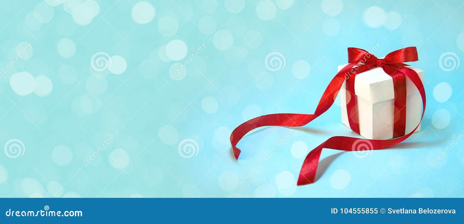 ` S del regalo de la Navidad en la caja blanca con la cinta roja en fondo azul claro Bandera de la composición del día de fiesta