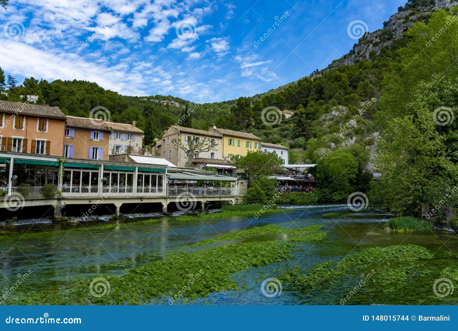 S?der av Frankrike, sikt p? den lilla Provencal staden av poeten Petrarch Fontaine-de-vaucluse med vatten f?r smaragdgr?splan av