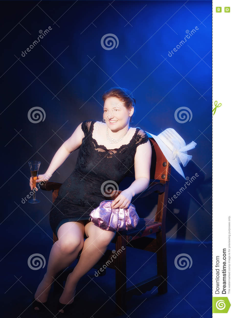Elegant redhead fat lady in an evening gown, sitting in an old, noble,  Spanish wooden chair. Studio recording with blue background