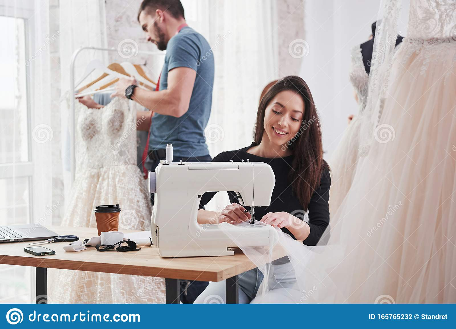 It S Important To Love Your Job Female Fashion Designer Works On The New Clothes In The Workshop With Man Behind Stock Photo Image Of Custom Busy 165765232
