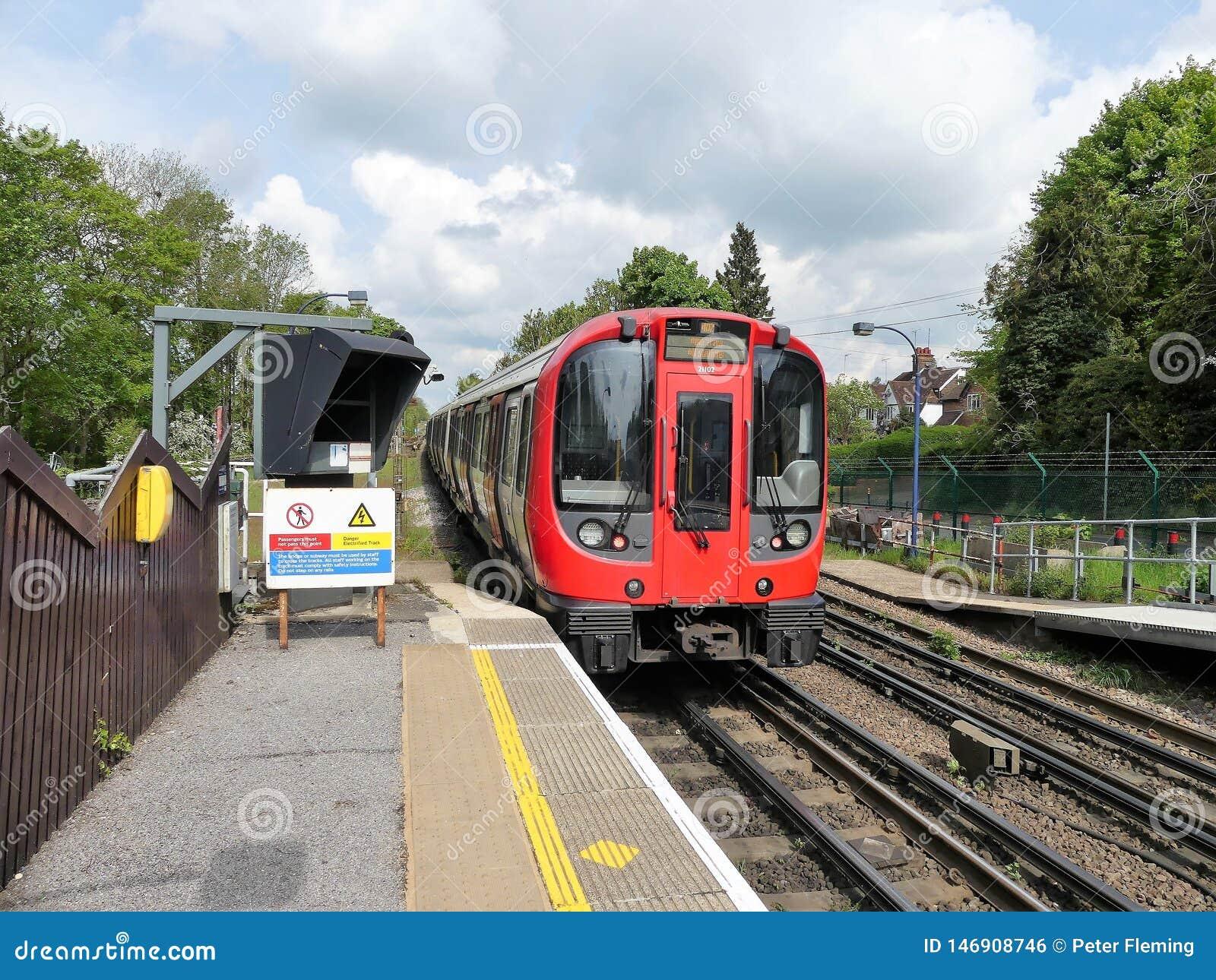 S8 lagerför London det underjordiska drevet som lämnar den Chorleywood stationen på den storstads- linjen järnväg