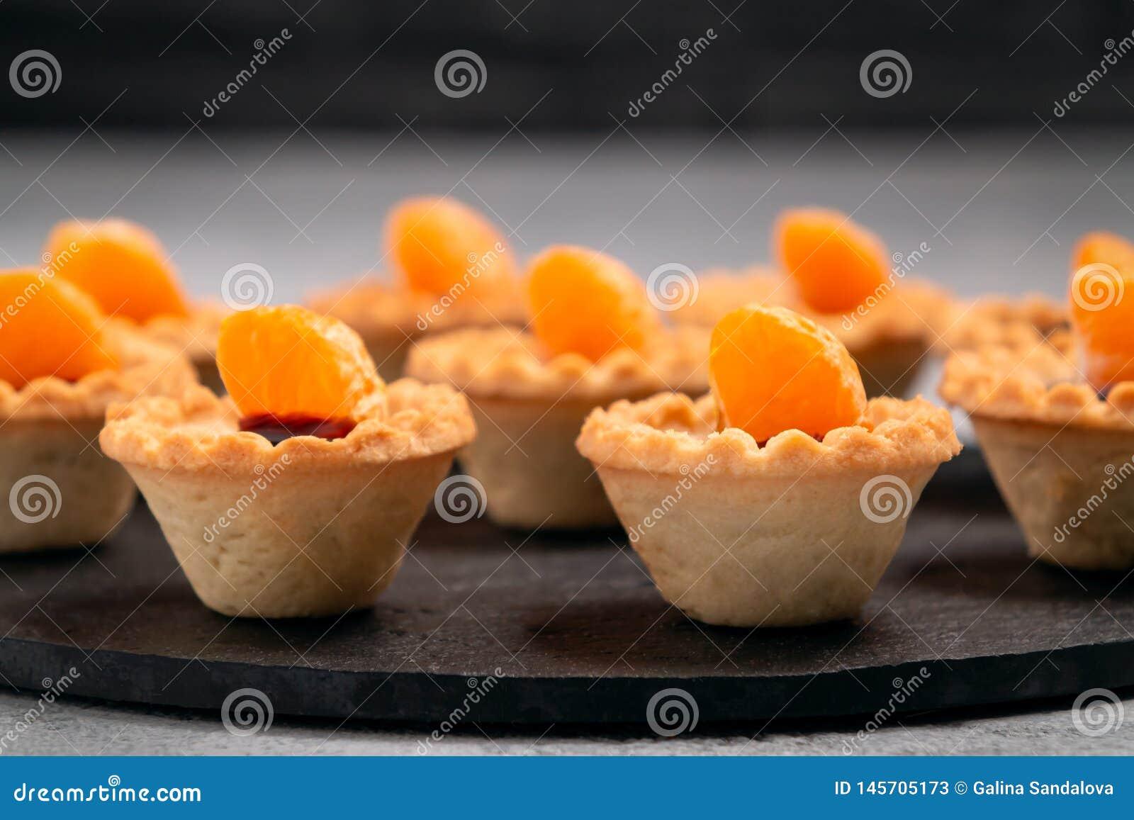 S?ta tartlets med choklad och skivor av tangerin p? en matr?tt av naturligt kritiserar f?r portion