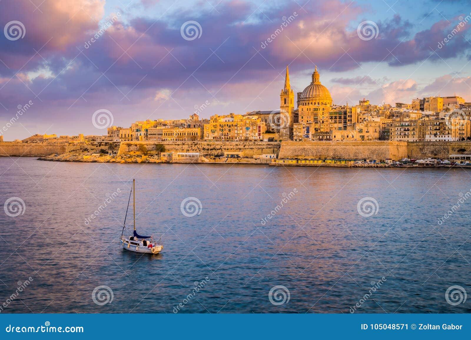 ` S Vallettas, Malta - StPaul-Kathedrale in der goldenen Stunde an Malta-` s Hauptstadt Valletta mit Segelboot und schönem buntem