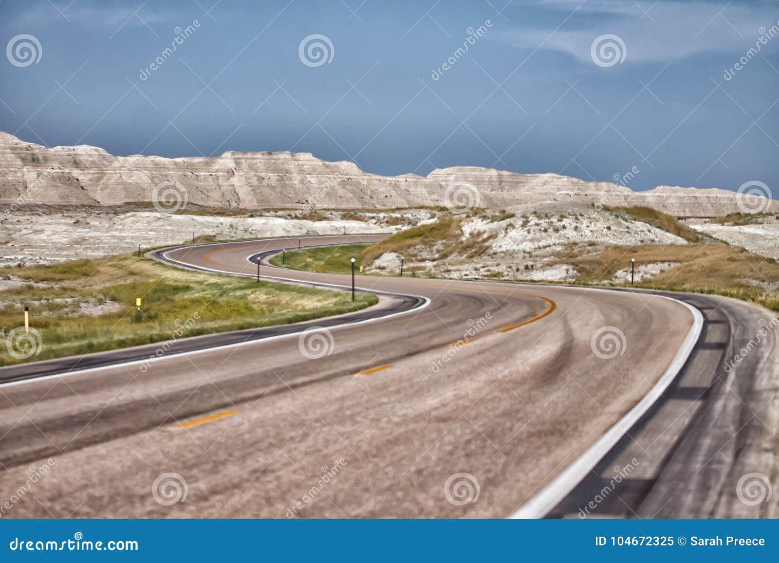 S wyginający się brukował drogę przez badlands Południowy Dakota