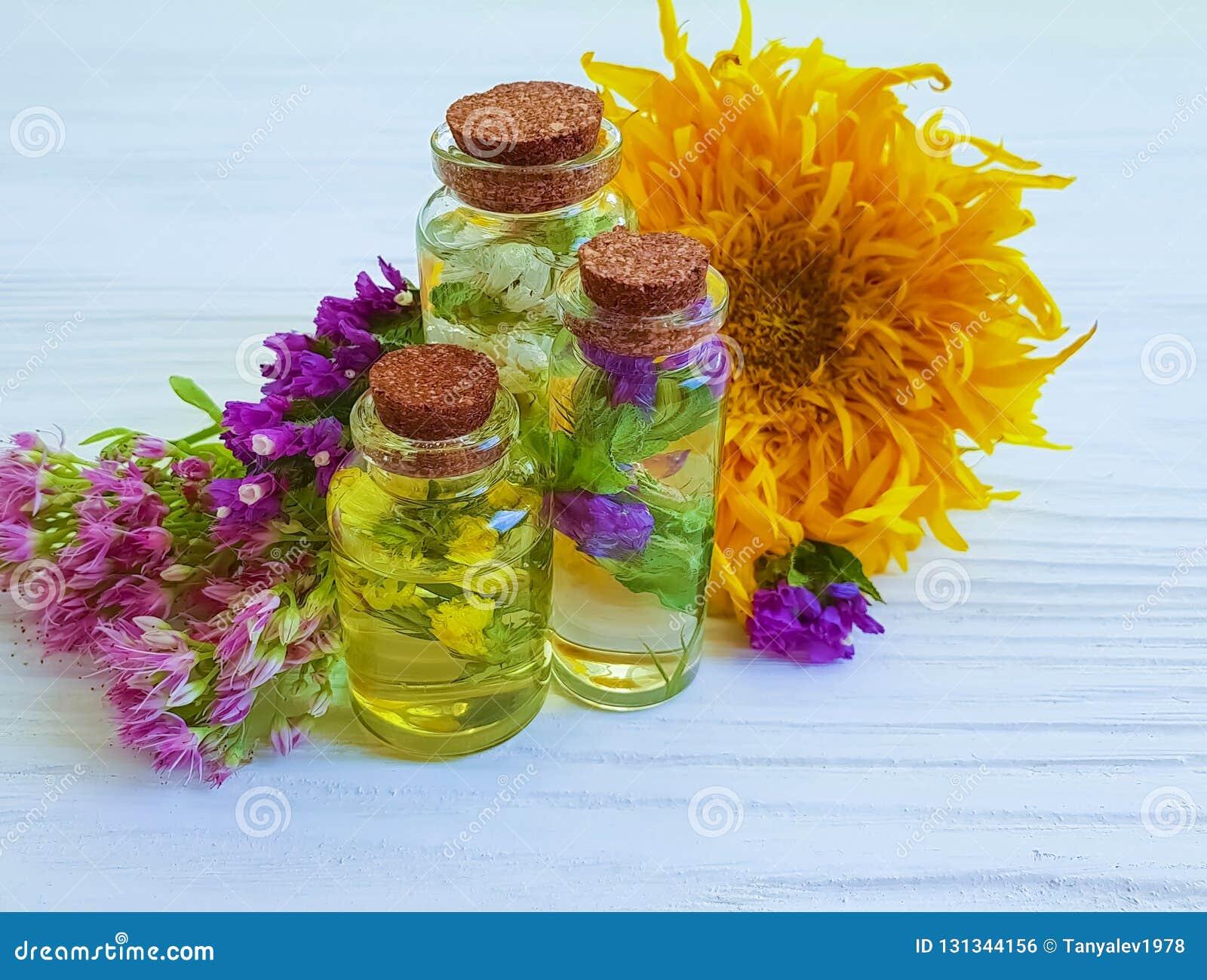 Saúde cosmética da essência, flores no fundo de madeira