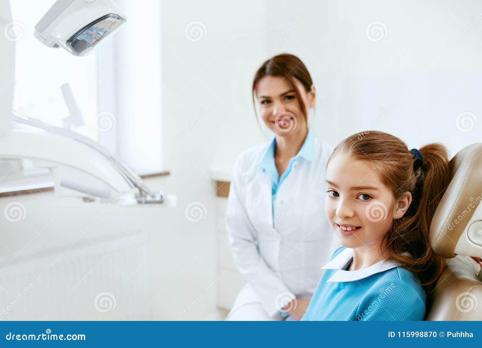 Saúde dental Dentista And Happy Girl no escritório da odontologia