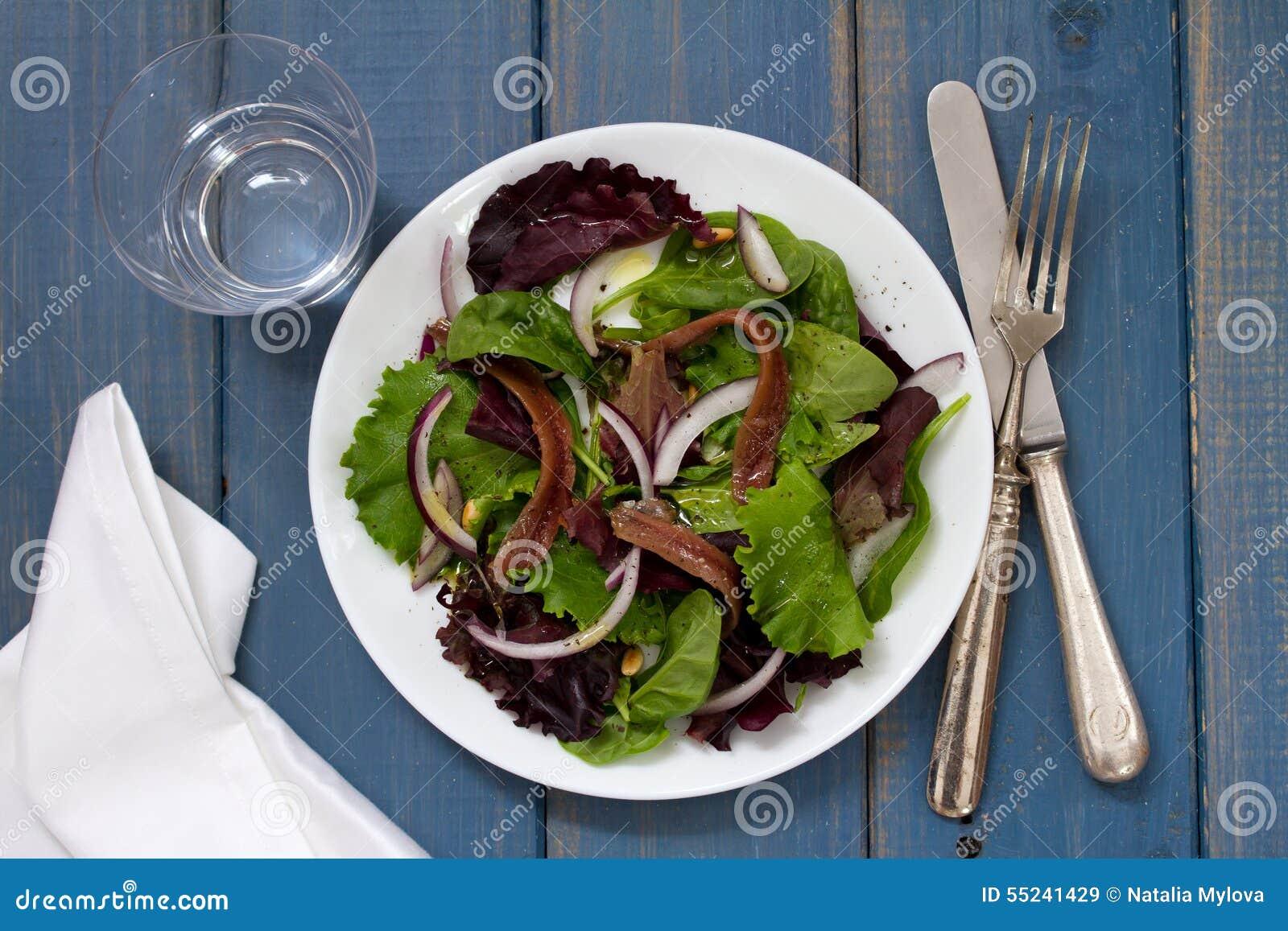 Sałatka z sardelami i cebulą na bielu talerzu na błękitnym tle