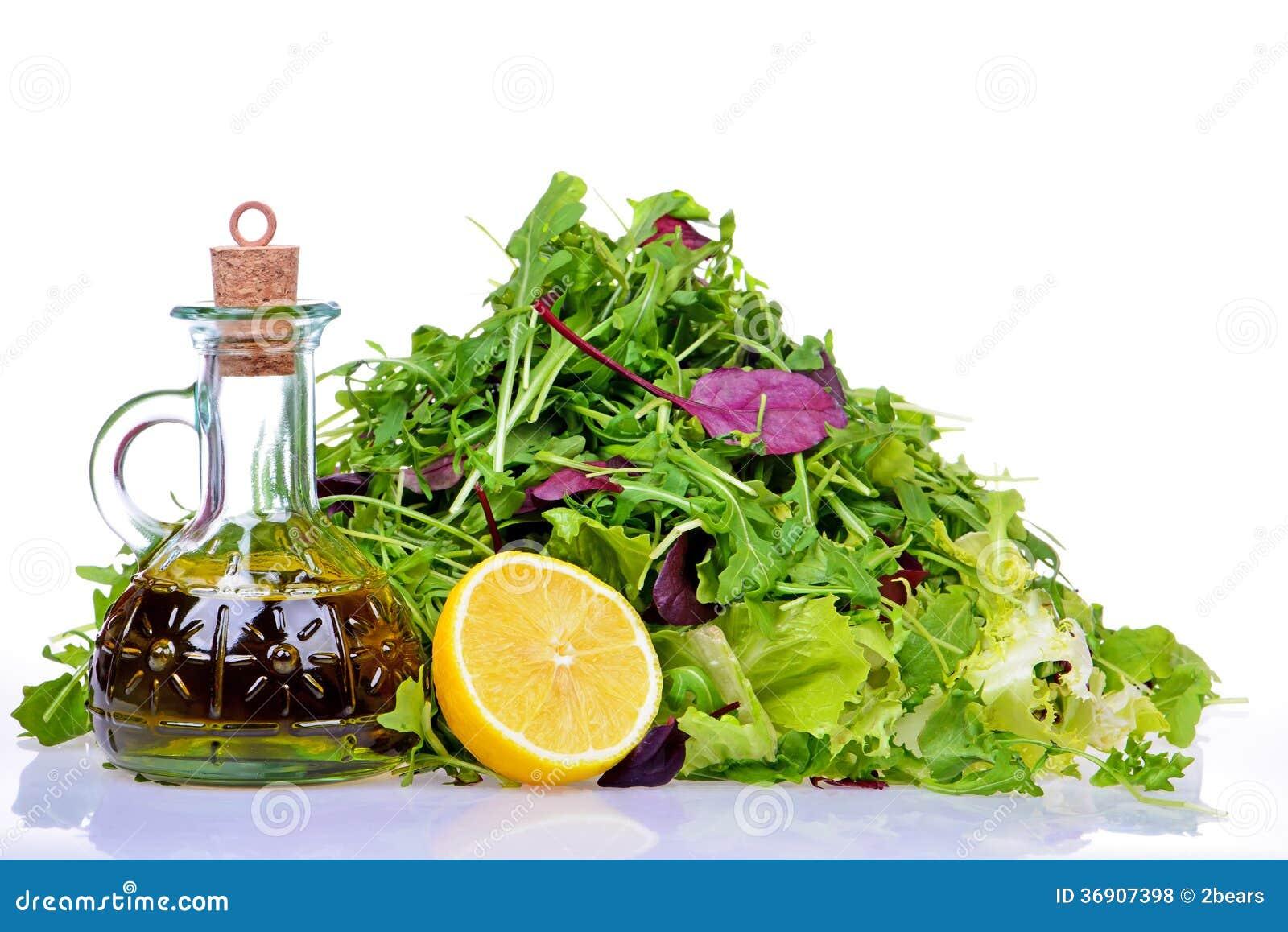 Sałatkowa mieszanka z butelką oliwa z oliwek i cytryna na bielu