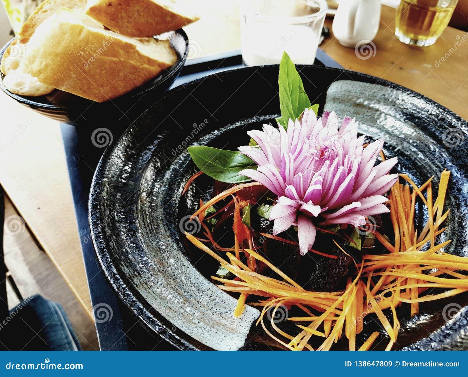 Sałatkowy naczynie z marchewka lampasami na czarnym talerzu z pięknym garnirunkiem, cebuli różą, liśćmi basil i baguette,