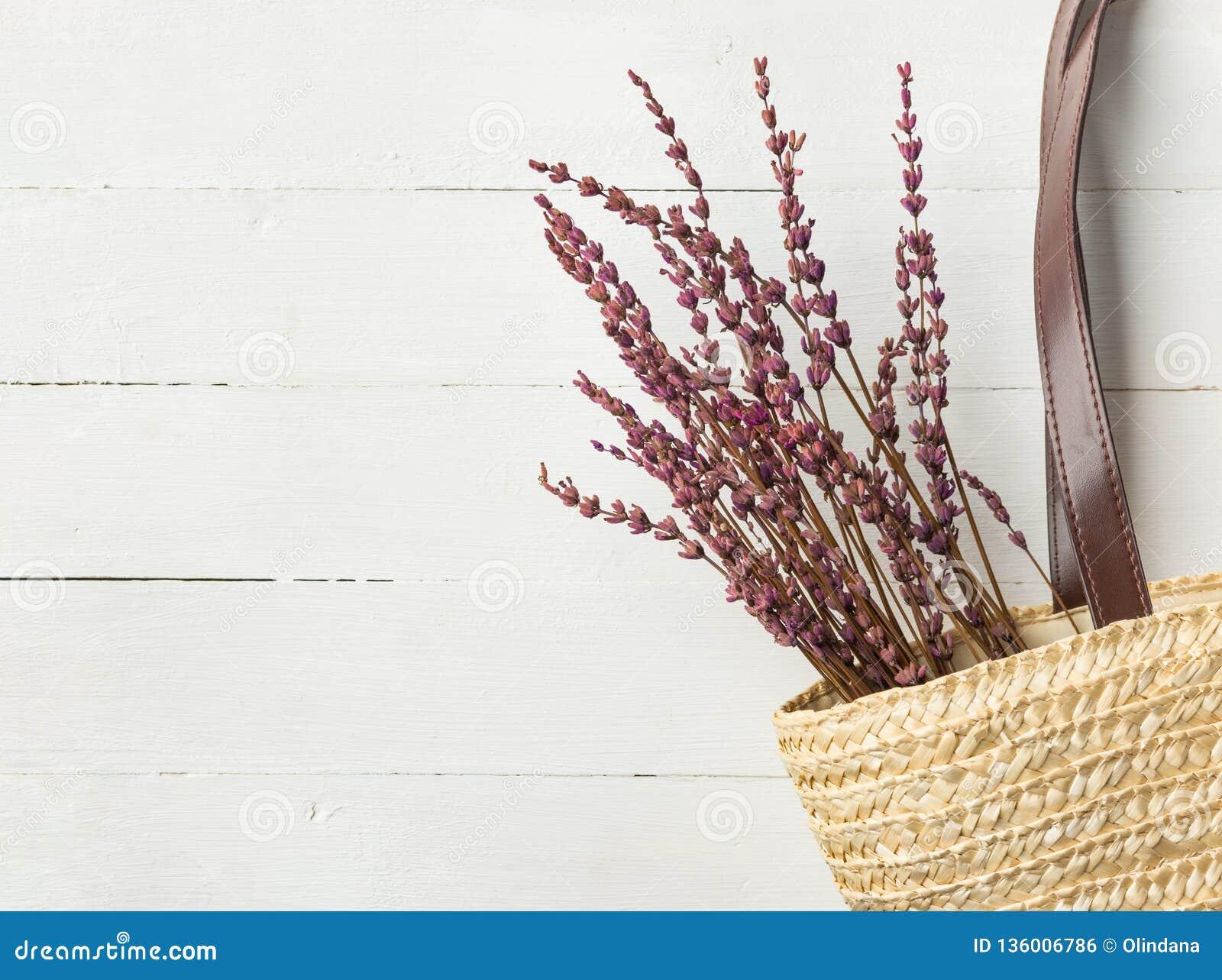 Sac d épaule tissé sur métiers à main de plage de paille avec le bouquet en cuir de fleurs de lavande de poignées sur le fond bla