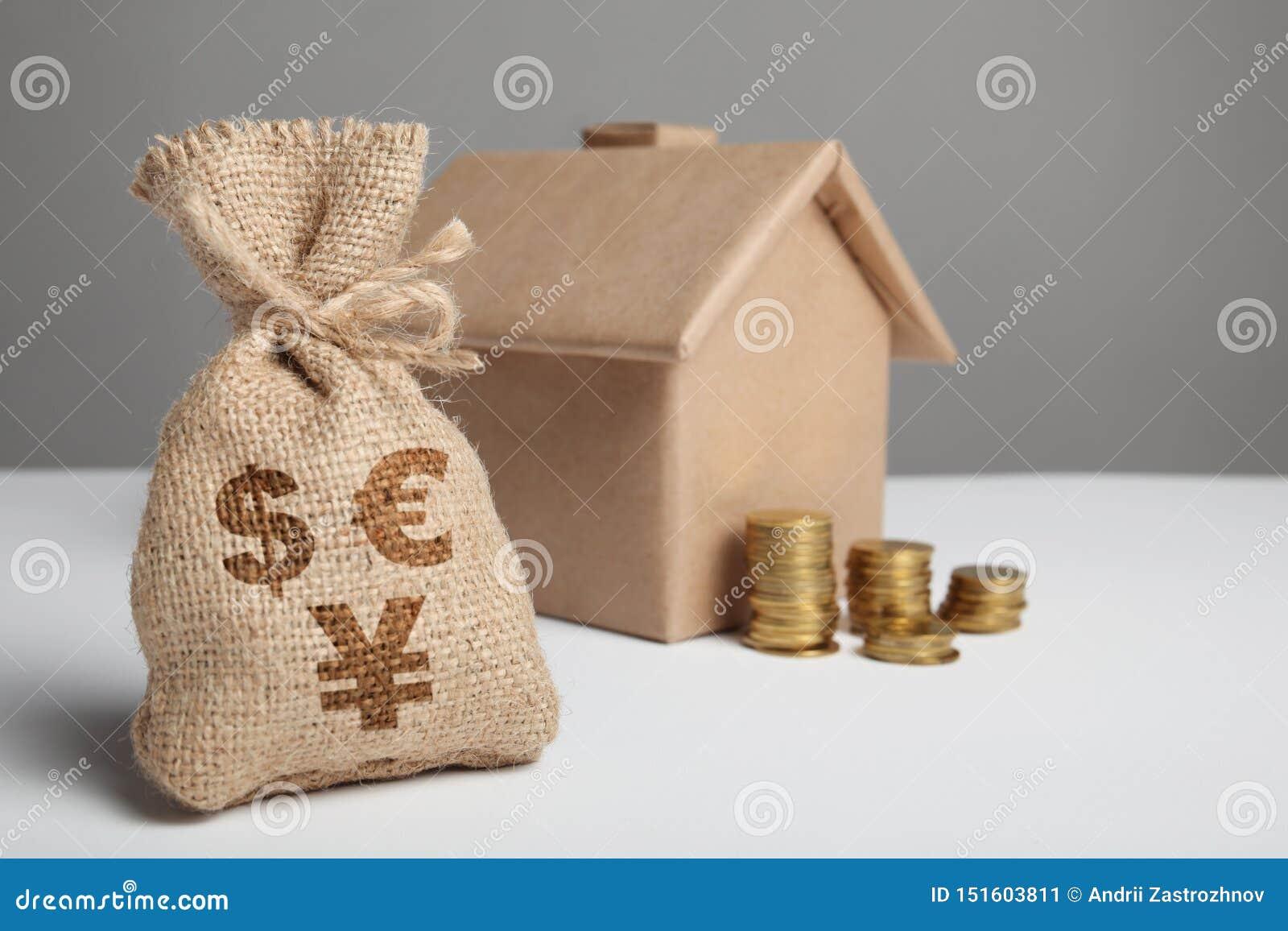 Sac de cru avec le signe du dollar, d euro et de yuans et les pièces de monnaie jaunes sur le fond du chiffre de métier de la mai