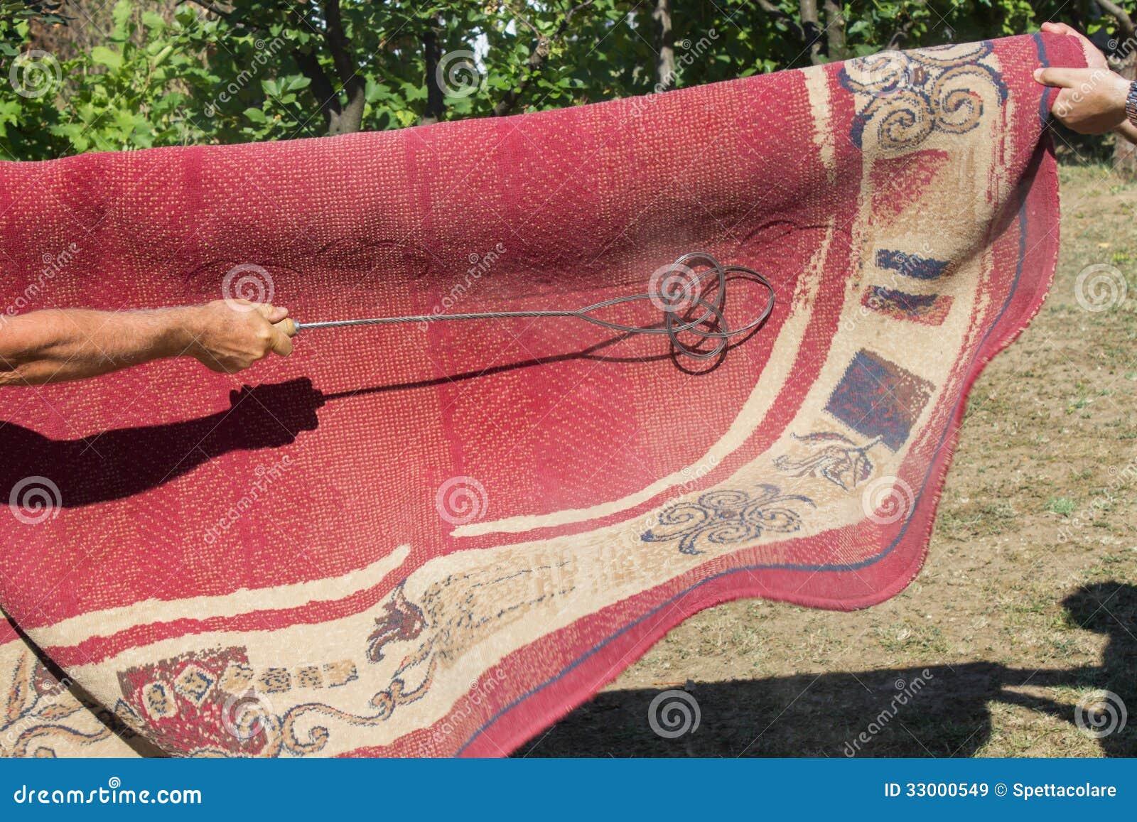 sacando-el-polvo-de-una-manta-el-m%C3%A9todo-tradicional-de-limpieza-de-la-alfombra-33000549.jpg