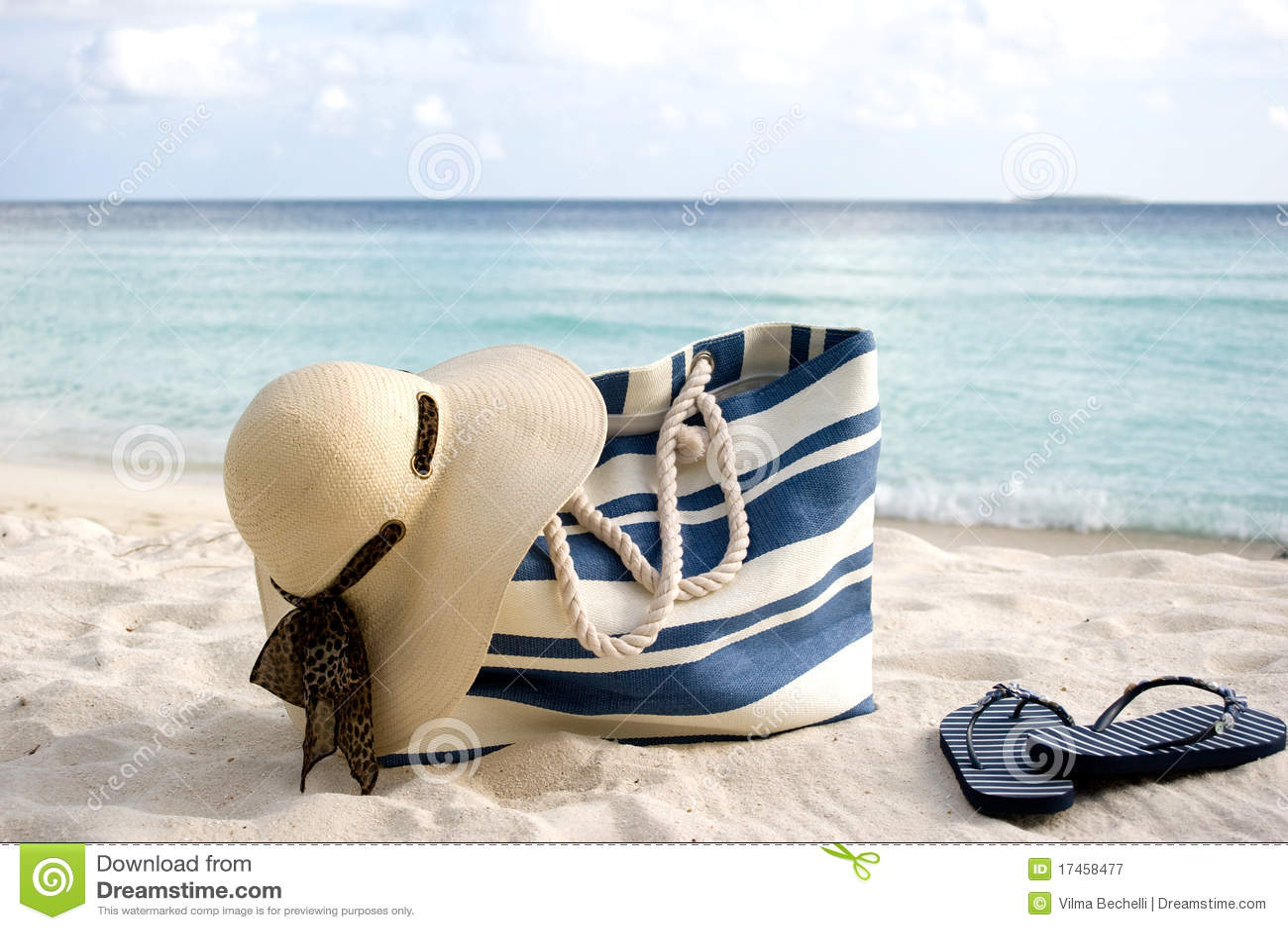 Sacchetto, cappello e flip-flop sulla spiaggia