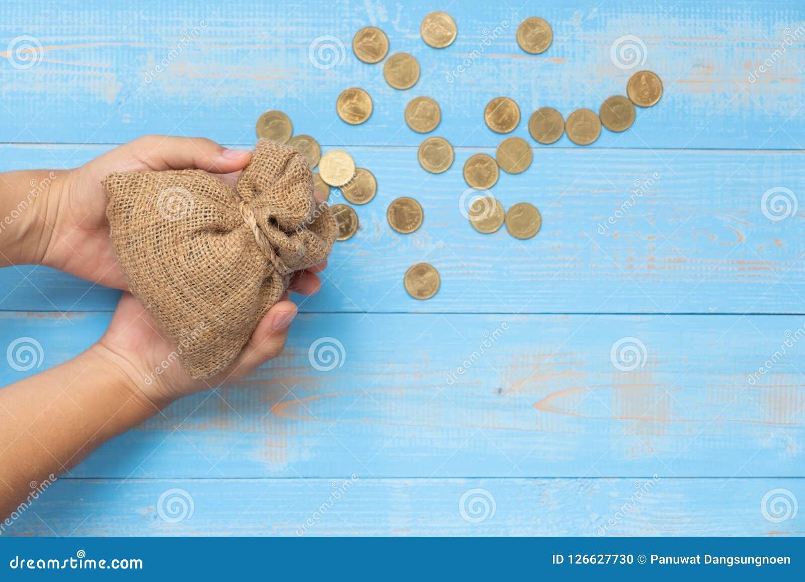 Sacco o sacchetto dei soldi della tenuta con le monete su fondo di legno blu