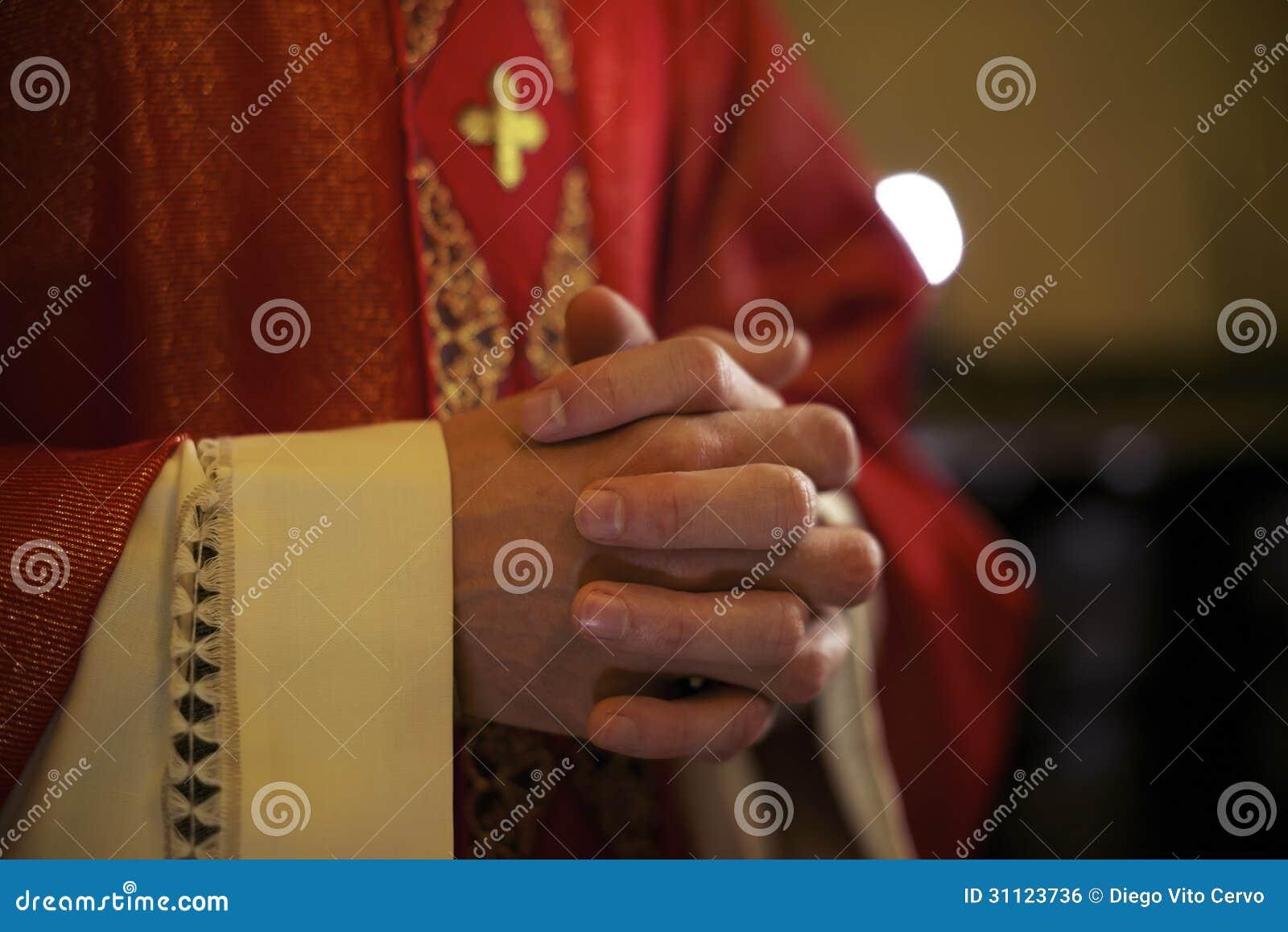 Sacerdote católico no altar que reza durante a massa