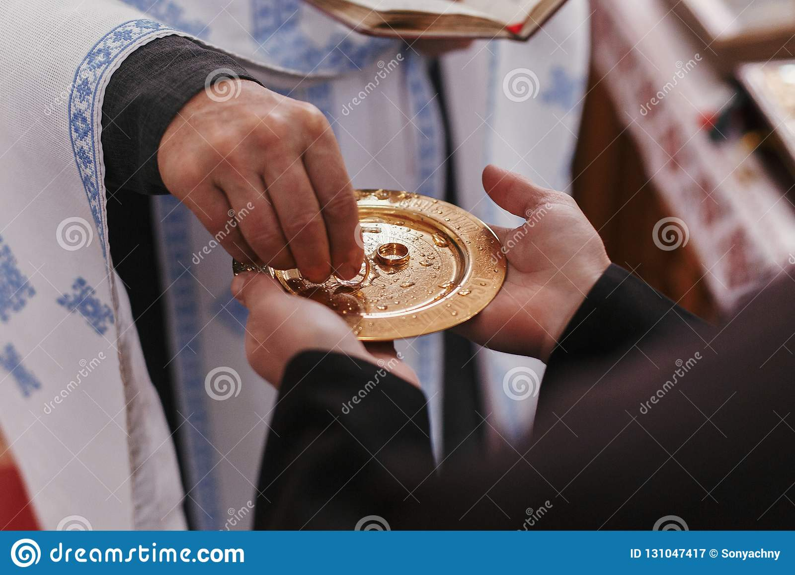 Sacerdote que toma el anillo de bodas de oro de la placa Matrimonio de la boda