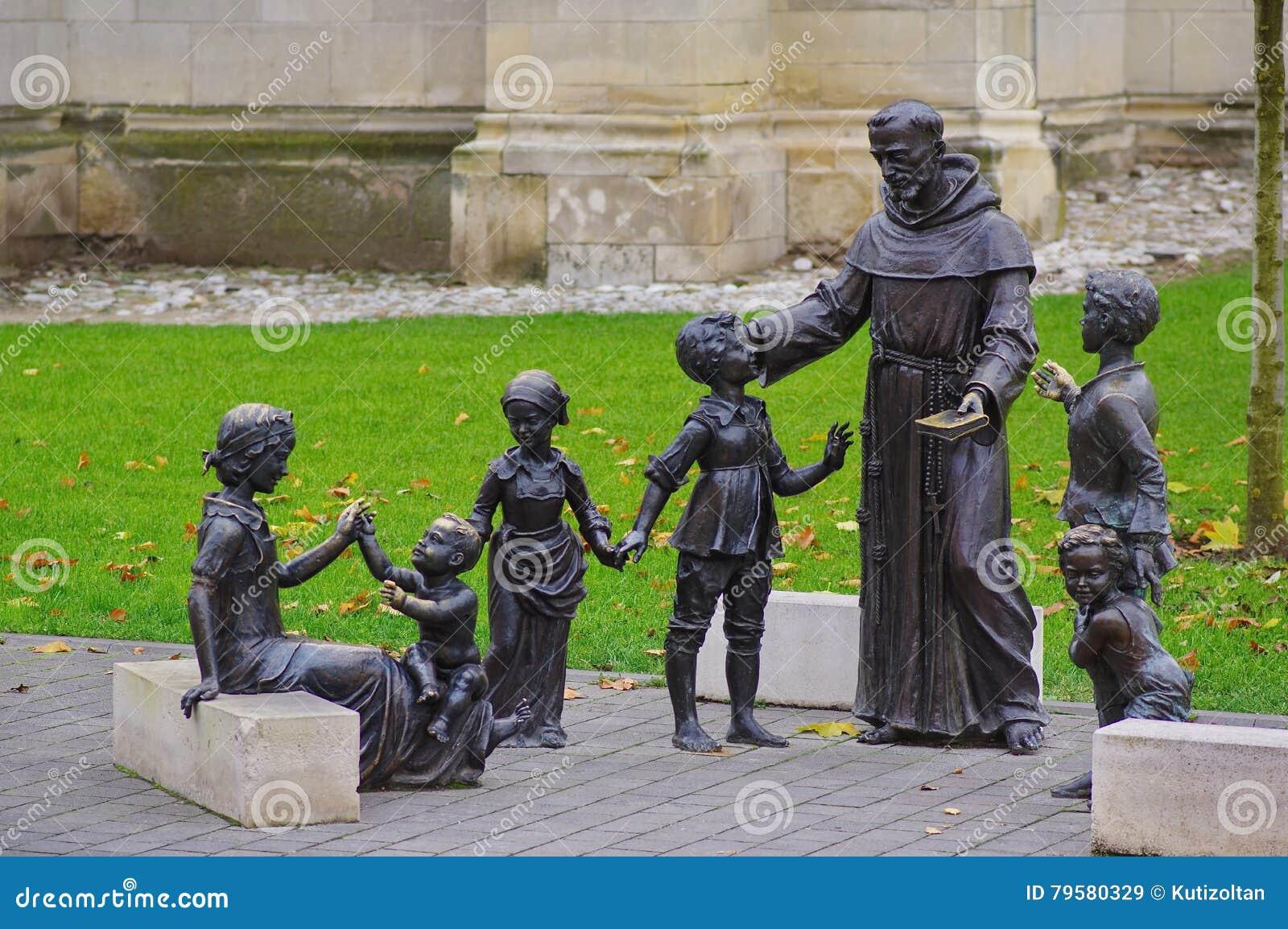Sacerdote y estatua de los niños