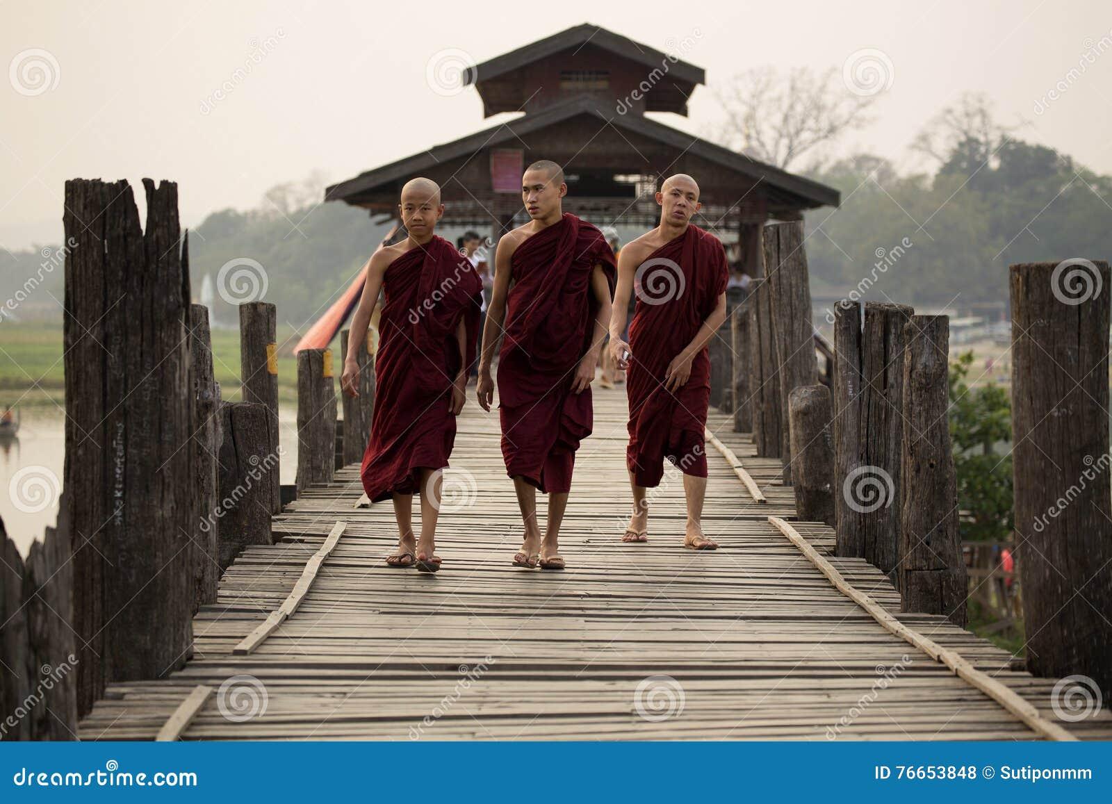 Sacerdotes o monjes que caminan en el puente de U Bein