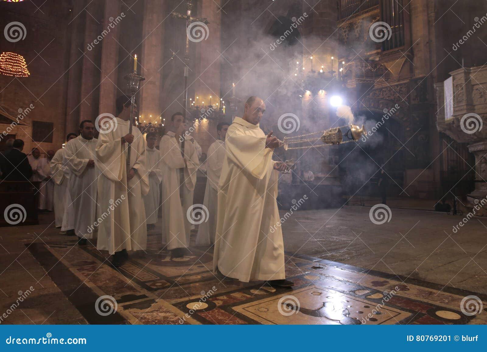 Sacerdotes y masa que entra del turíbulo del incienso