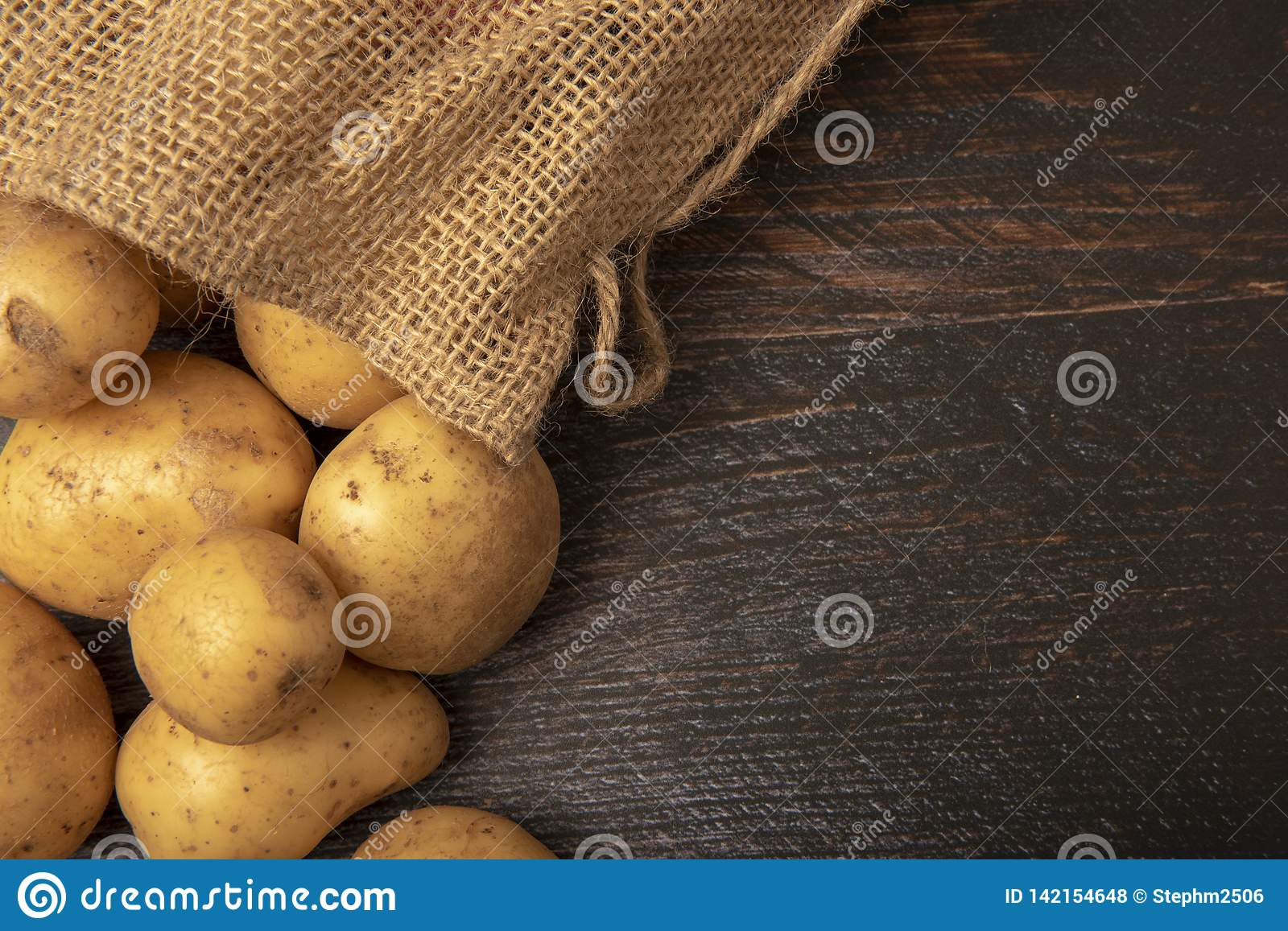 Sack of potatoes on wooden background