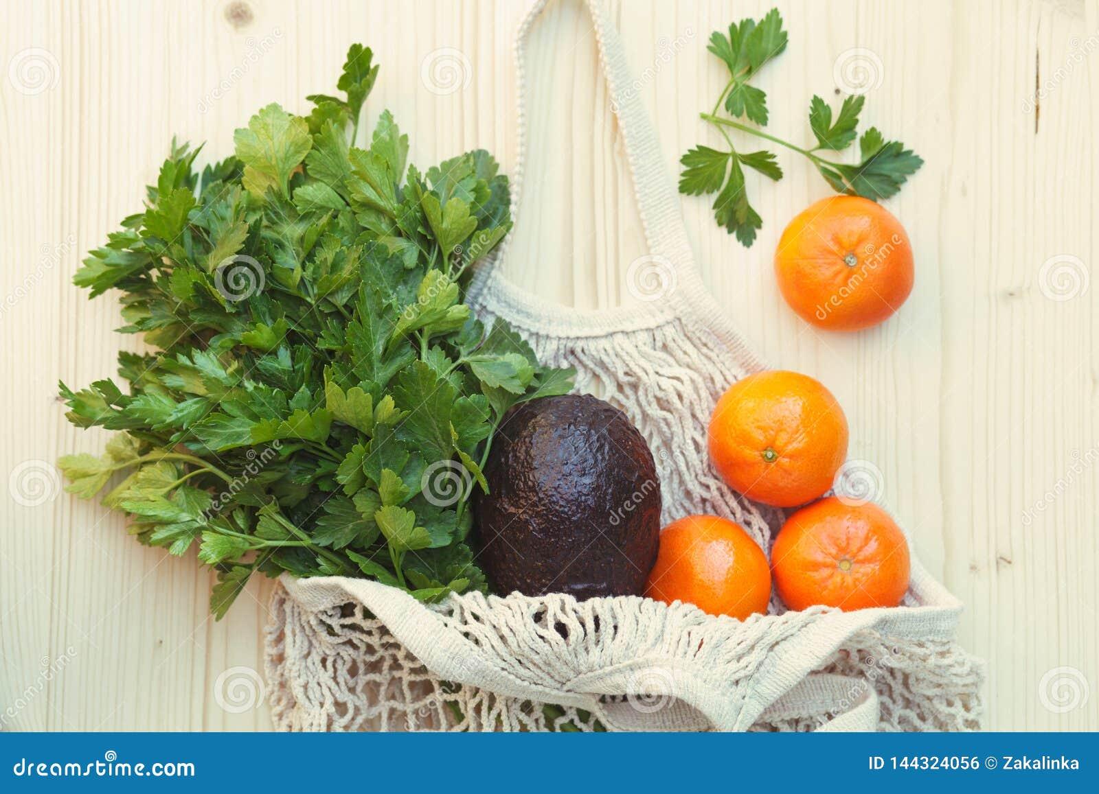 Saco de corda reusável eco-amigável branco com frutos frescos, ervas e vegetais, abacate, salsa, laranjas no fundo de madeira