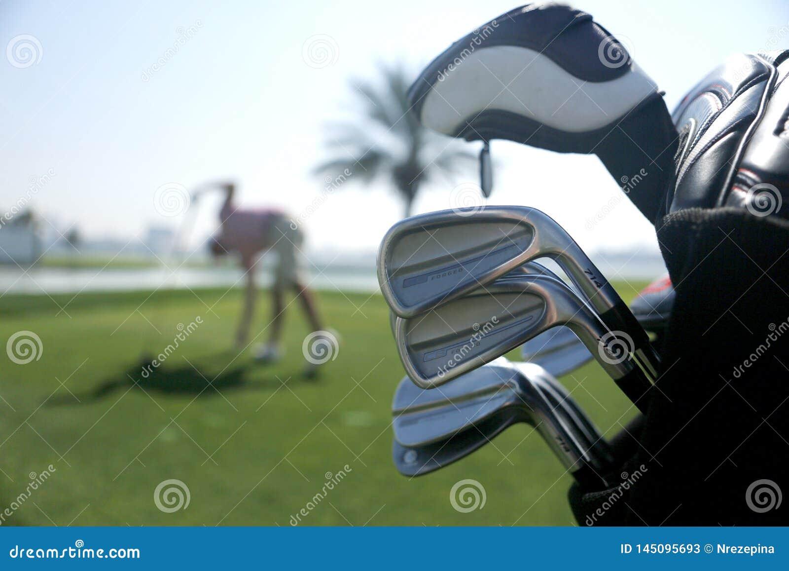 Saco de golfe com os clubes no plano e com o jogador antes do balanço no fundo