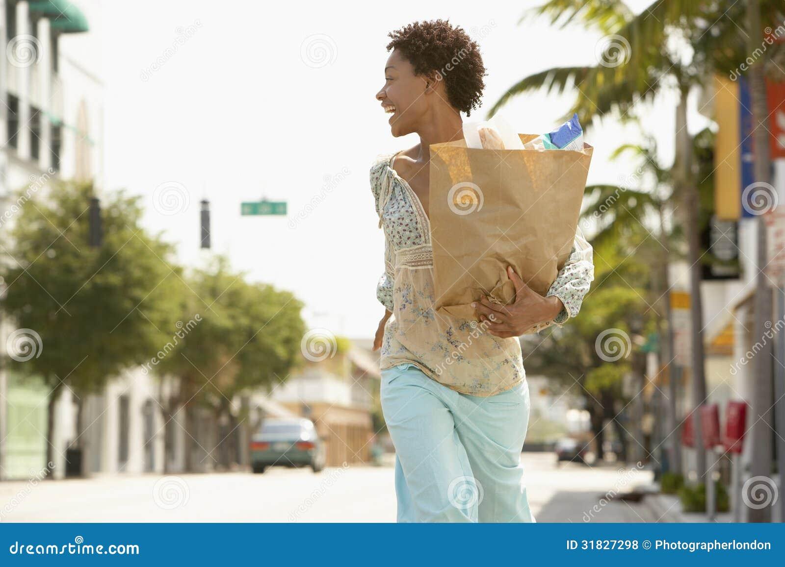 Saco de mantimento levando da mulher ao andar na rua